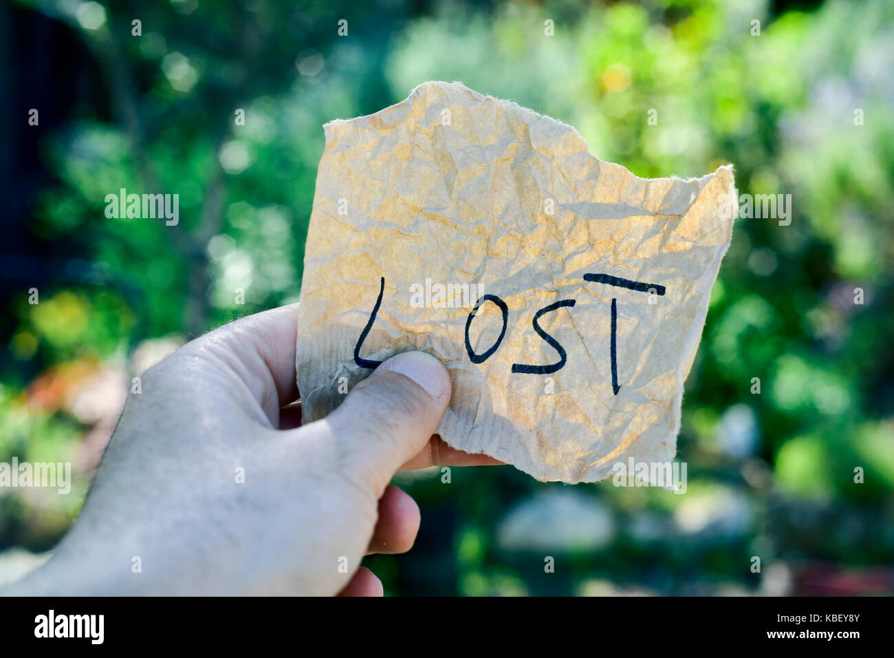 closeup of a caucasian man in the forest, with a note with the text lost in his hand - Stock Image