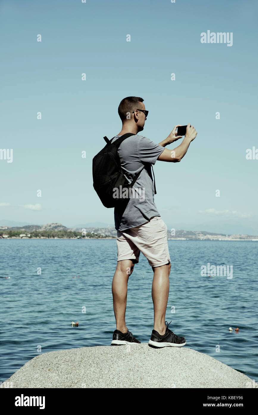 closeup of a young caucasian man carrying a backpack taking a photo of the sea in the Costa Smeralda, in Sardinia, - Stock Image