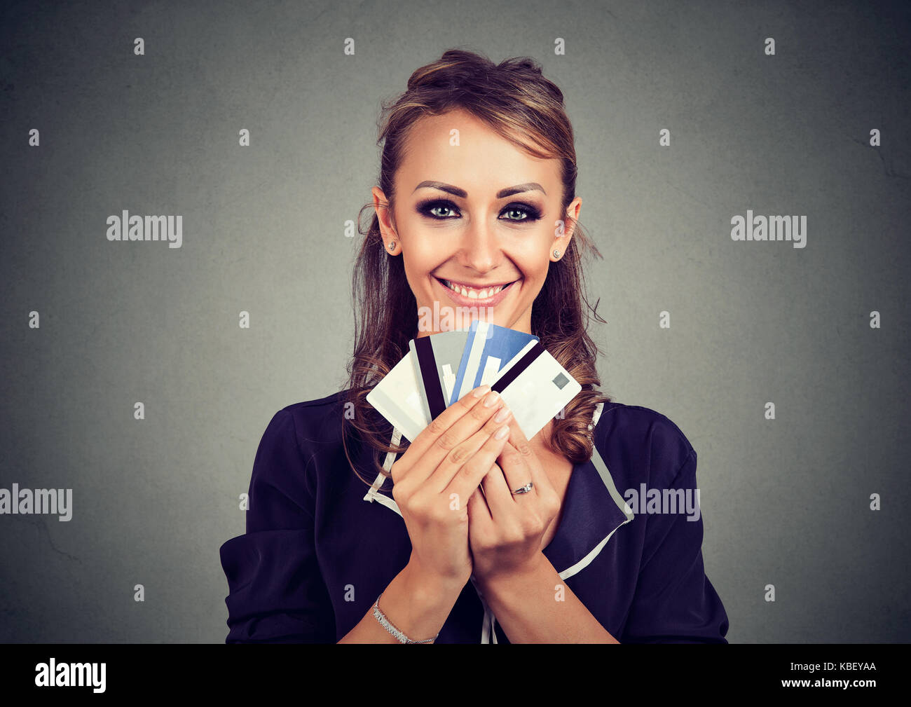 Woman with many different credit loyalty discount cards isolated on gray wall background. Stock Photo