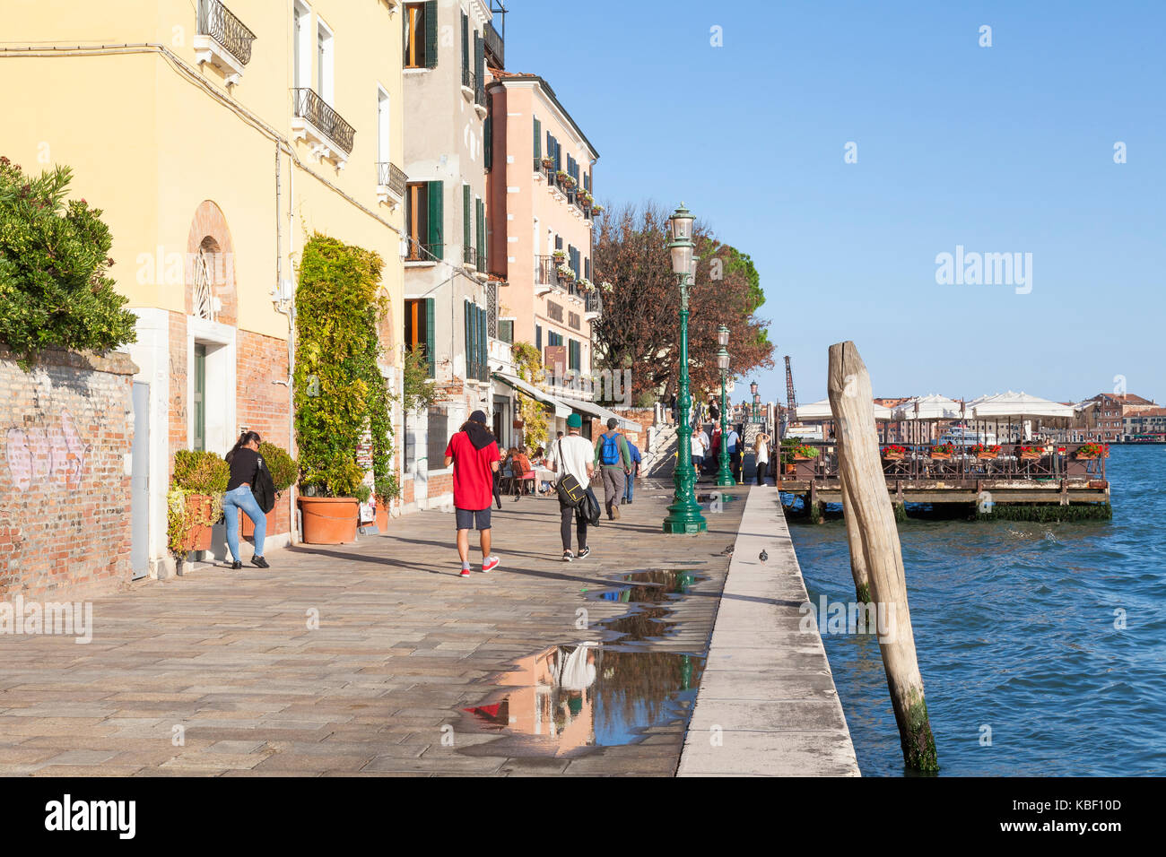 Zattere, Dorsoduro, Venice, Veneto, Italy in late evening light  with tourists walking and eating at an open air - Stock Image