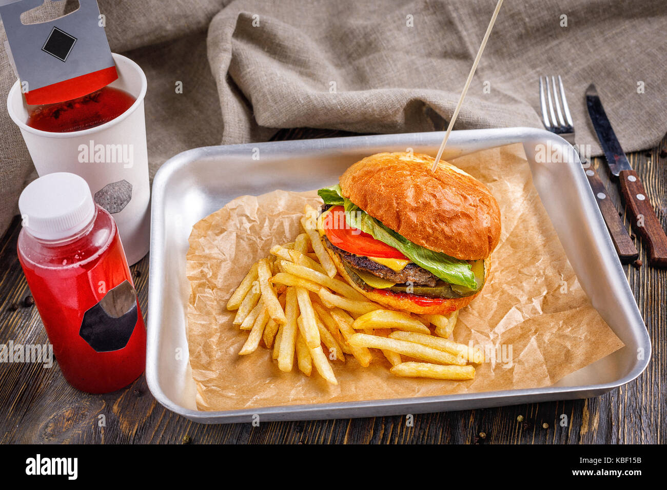 Big hamburger with three beef cutlet and vegetables with golden crispy french fries and toasted crispy toast on Stock Photo