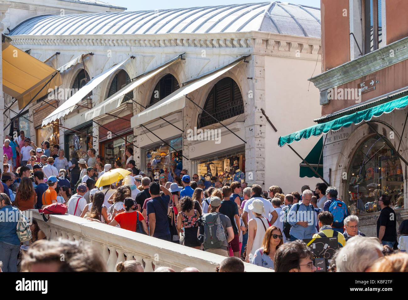 Crowds of tourists thronging the steps of the Rialto Bridge, San Marco, Venice, Italy in front of the row of little - Stock Image