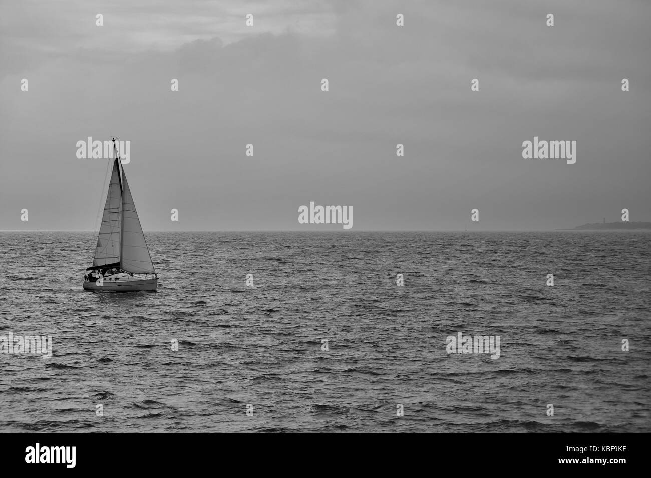 Felixstowe, UK. 29th Sep, 2017. Sailing dinghy heading for Felixstowe seen from Landguard Point. Cloudy and overcast - Stock Image