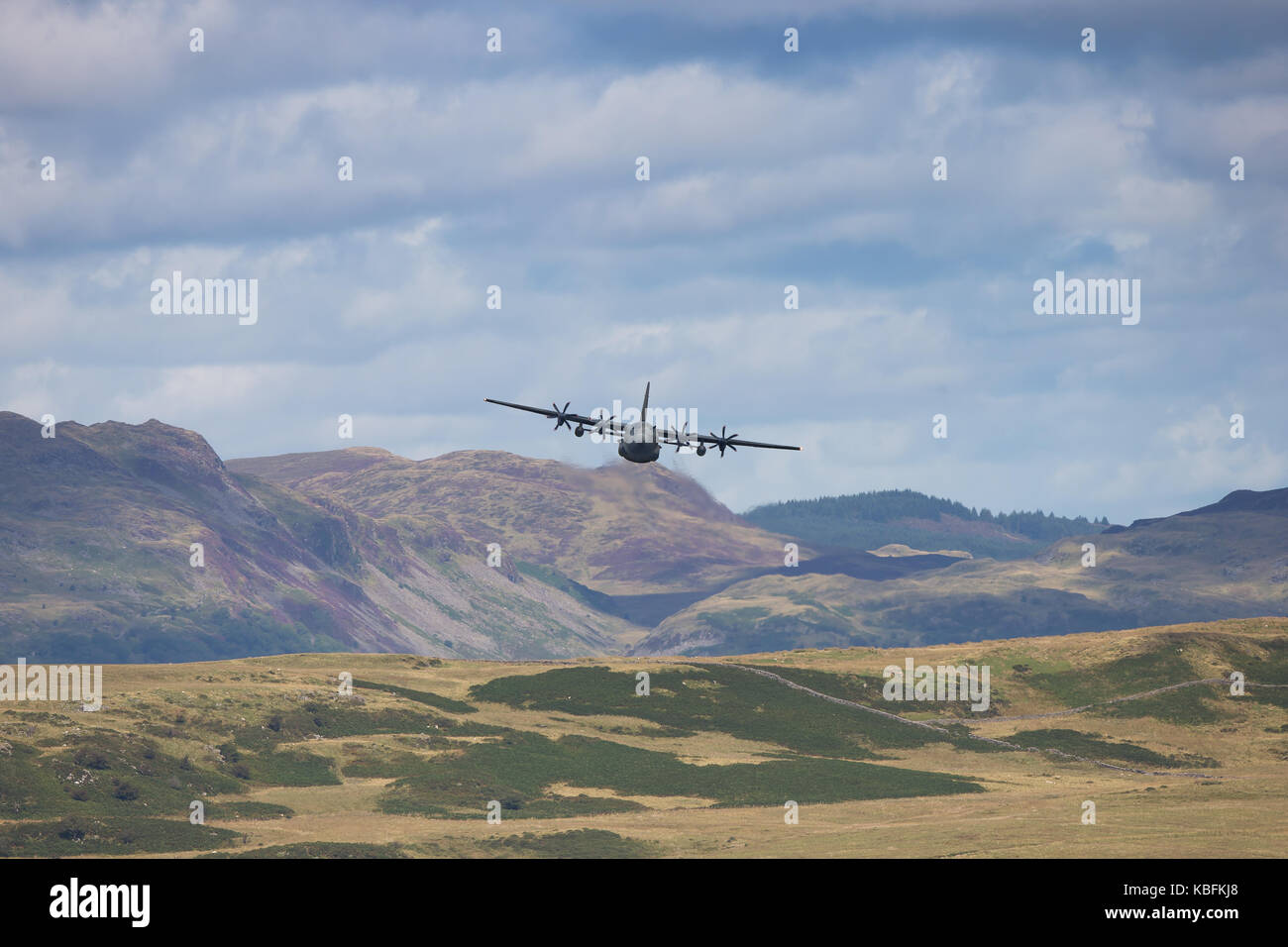 A low-flying Hercules aircraft heading towards the camera; Welsh mountains in the background & cloudy sky create - Stock Image
