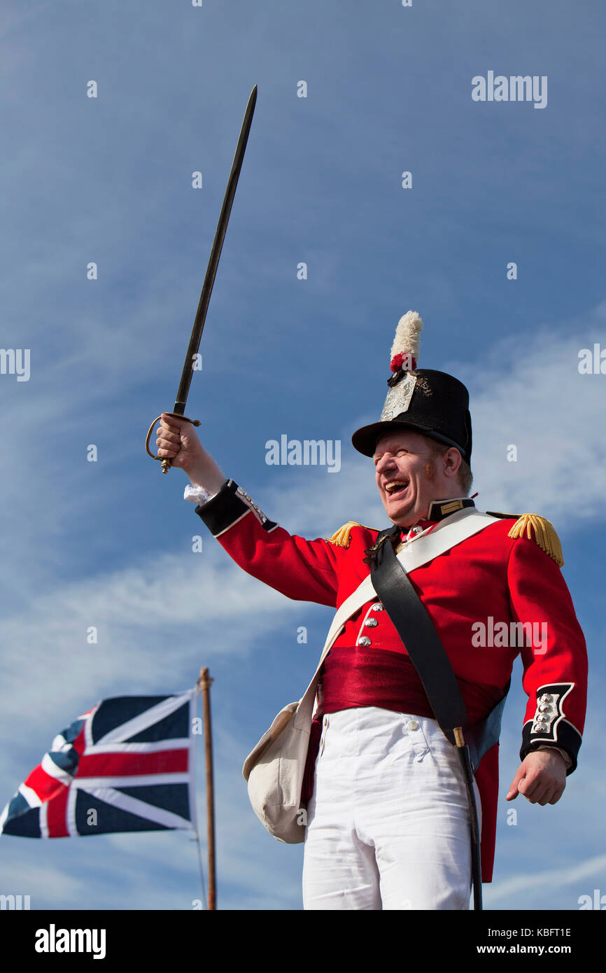 Red coat British Army officer with sword drawn overhead - Stock Image