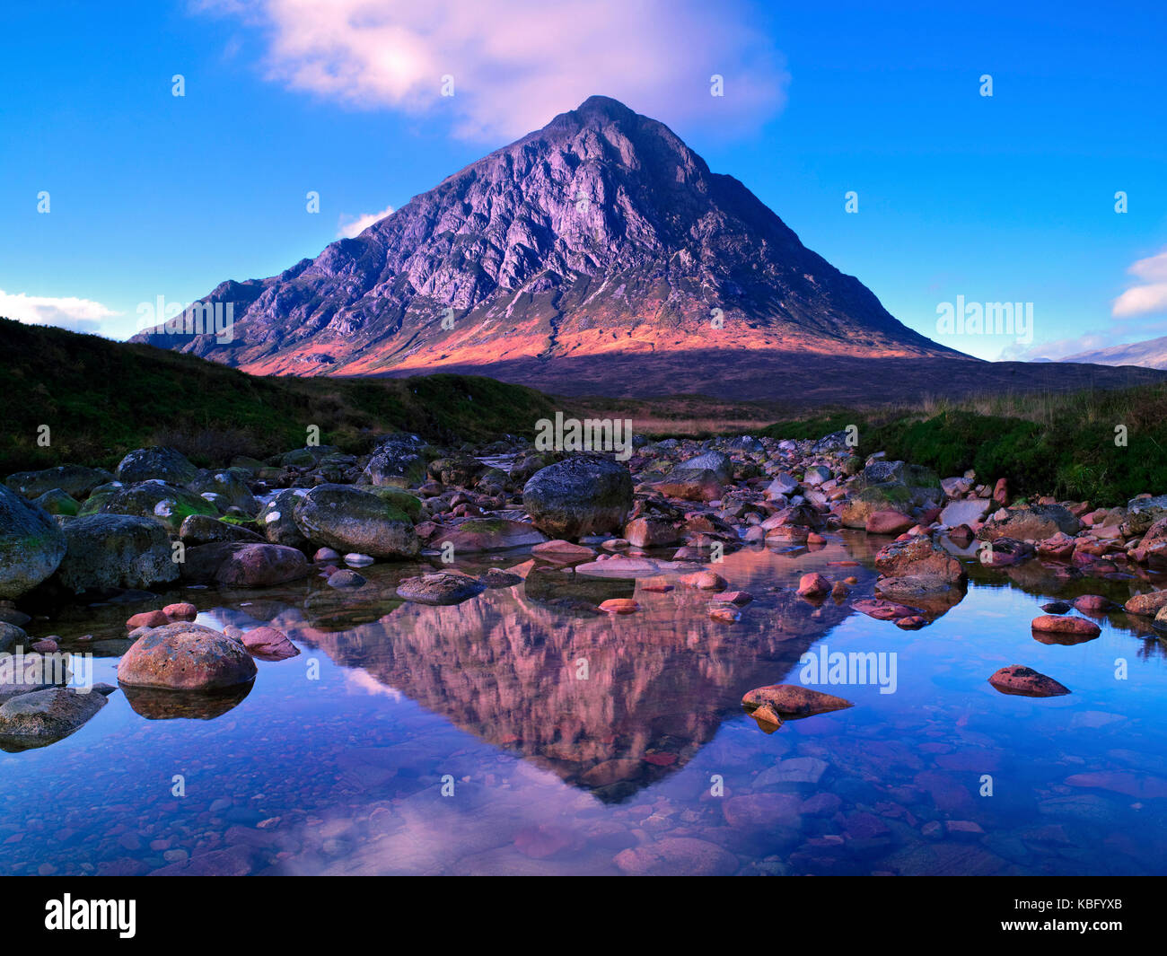 A sunny view of the famous mountain Buachaille Etive Mor and its reflection, on Rannoch Moor in the Scottish Highlands - Stock Image