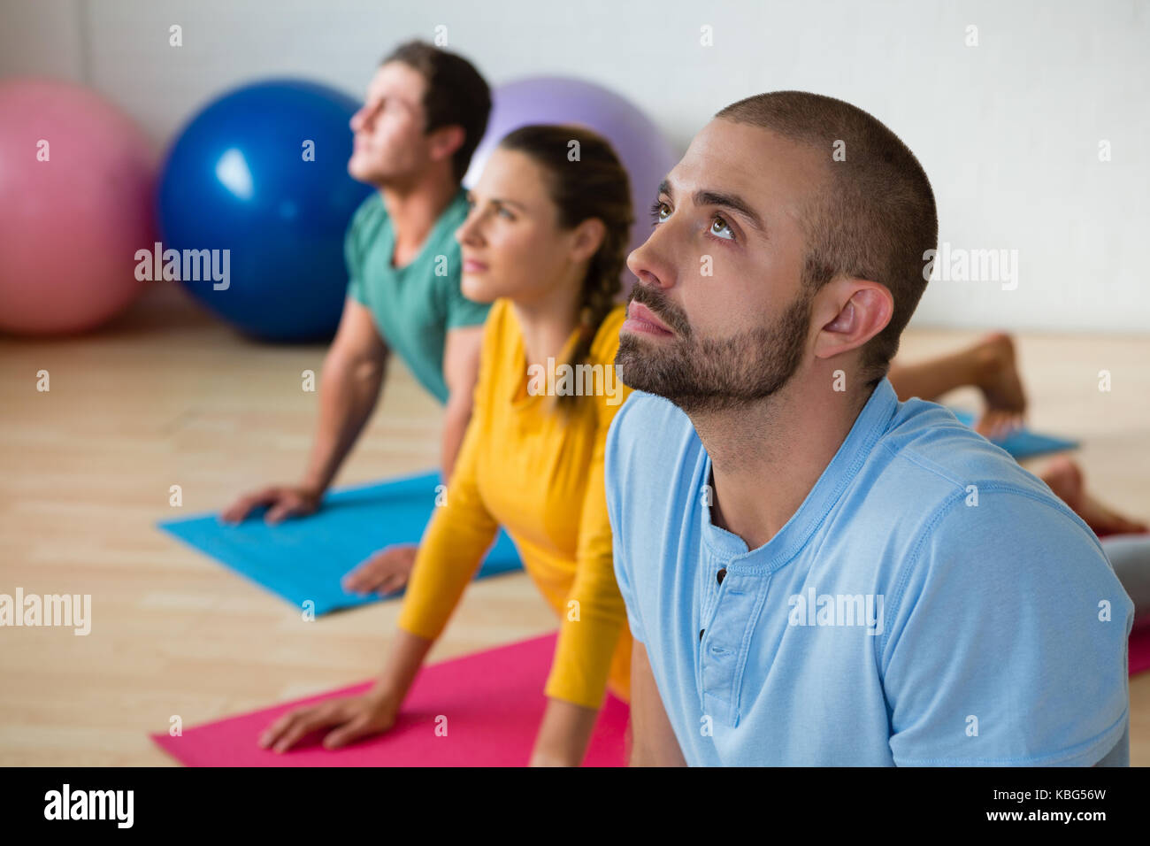 Yoga instructor guiding students in practicing cobra pose at health club - Stock Image