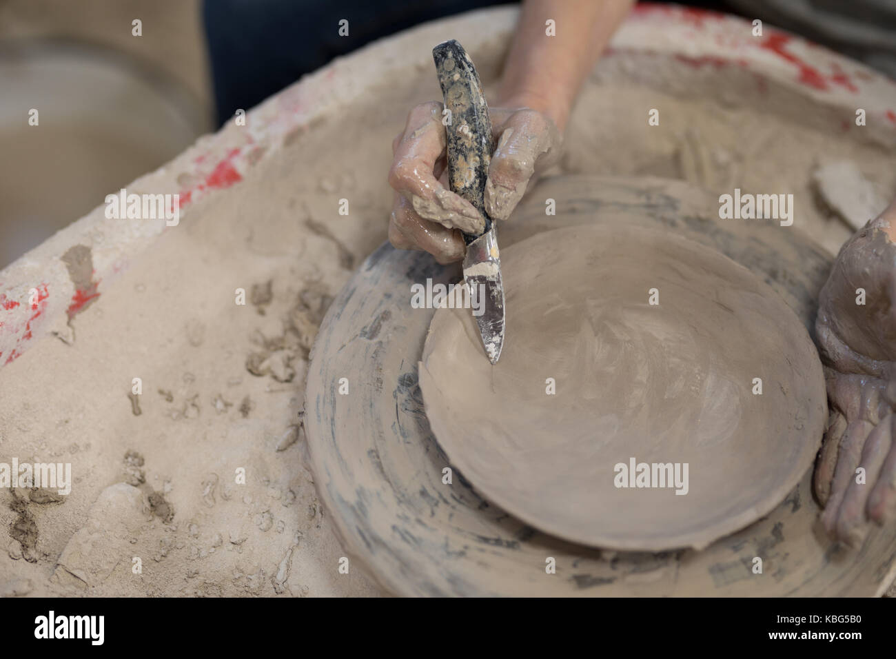 Female potter molding plate with hand tool in pottery workshop - Stock Image