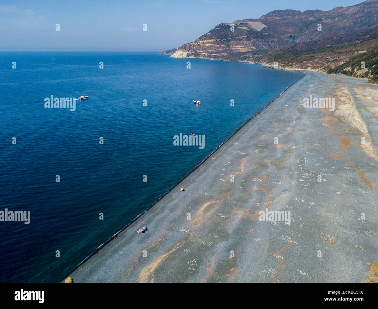 Aerial view of the black pebble beach, Nonza, Geometric designs made with stones, sailboats and moored boats near - Stock Image