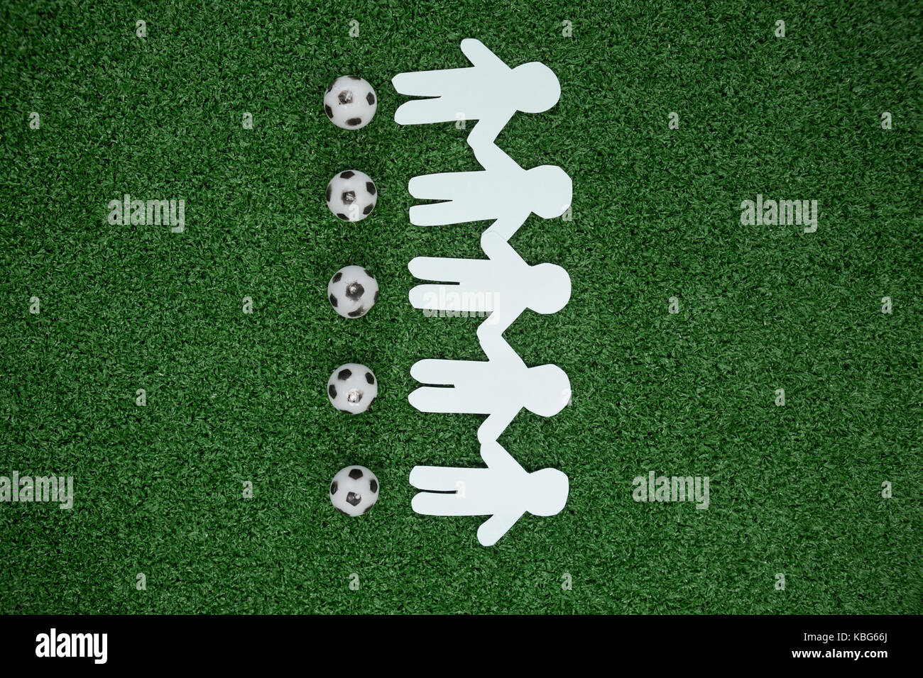 Overhead view of paper cut outs and footballs arranged on artificial grass - Stock Image