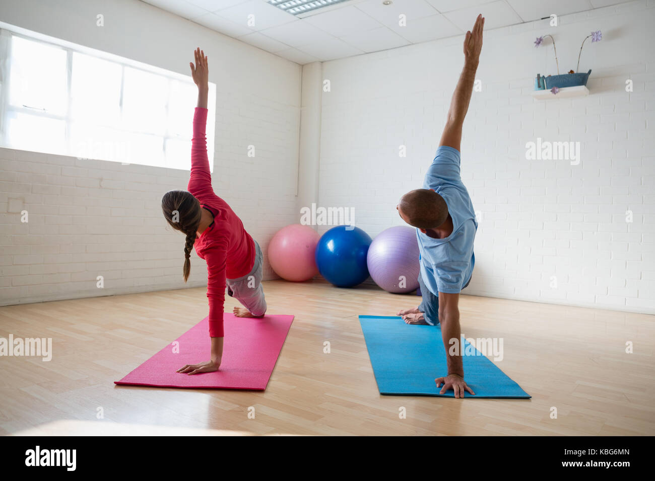 Instructor with female student practicing side plank pose in yoga studio - Stock Image