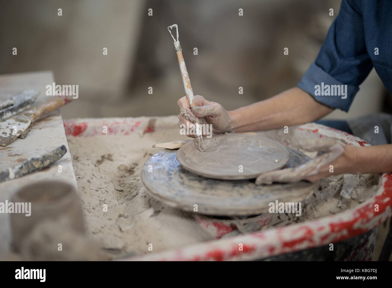 Close-up of female potter molding plate with hand tool - Stock Image