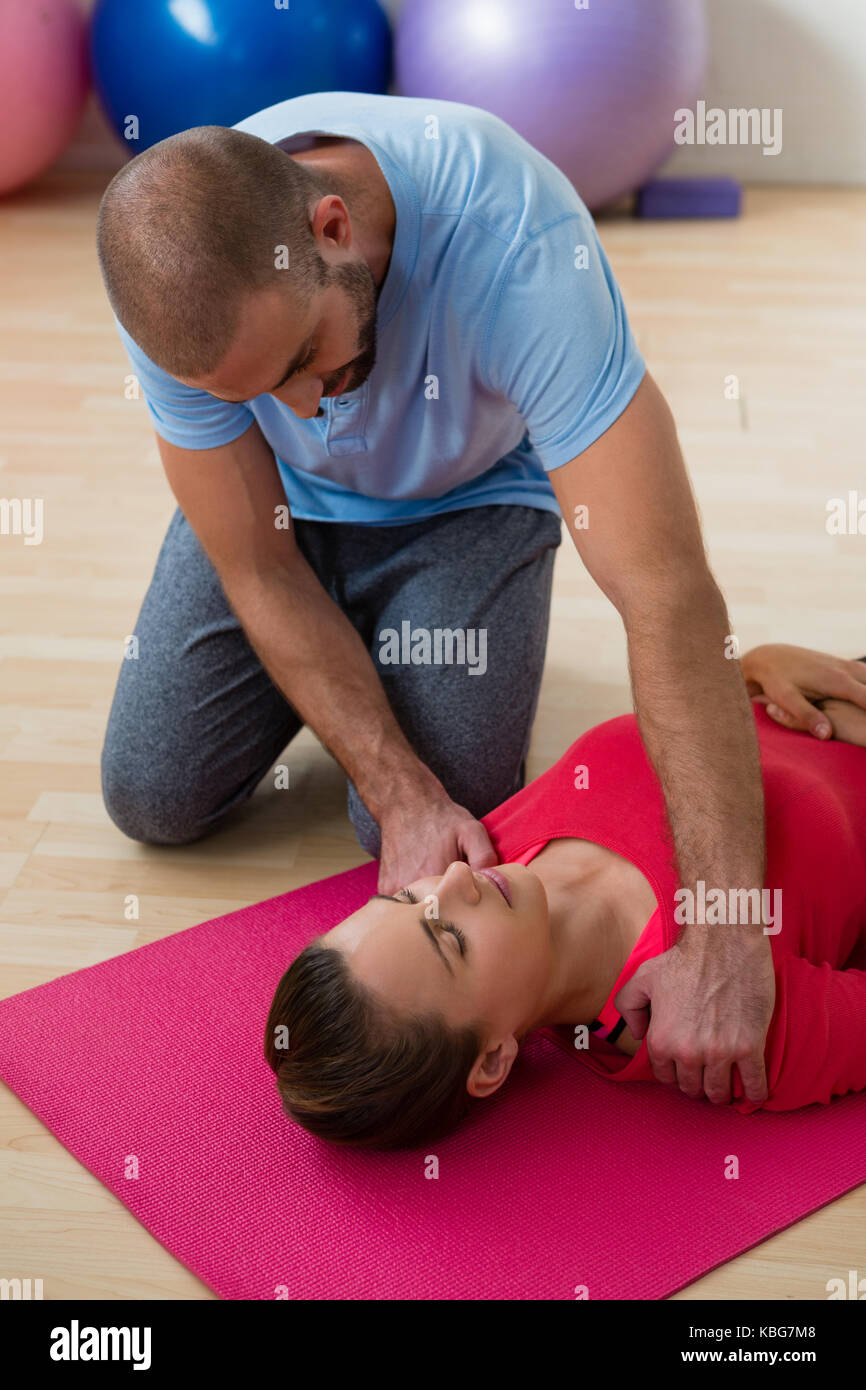 Yoga instructor guiding female student in exercising at health club - Stock Image