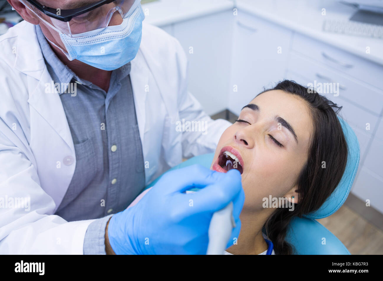 High angle view of dentist holding tools while treating woman at medical clinic - Stock Image