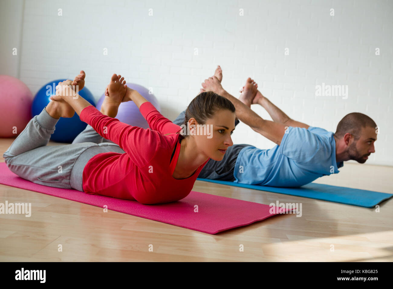 Female student practicing bow pose with instructor in yoga studio - Stock Image