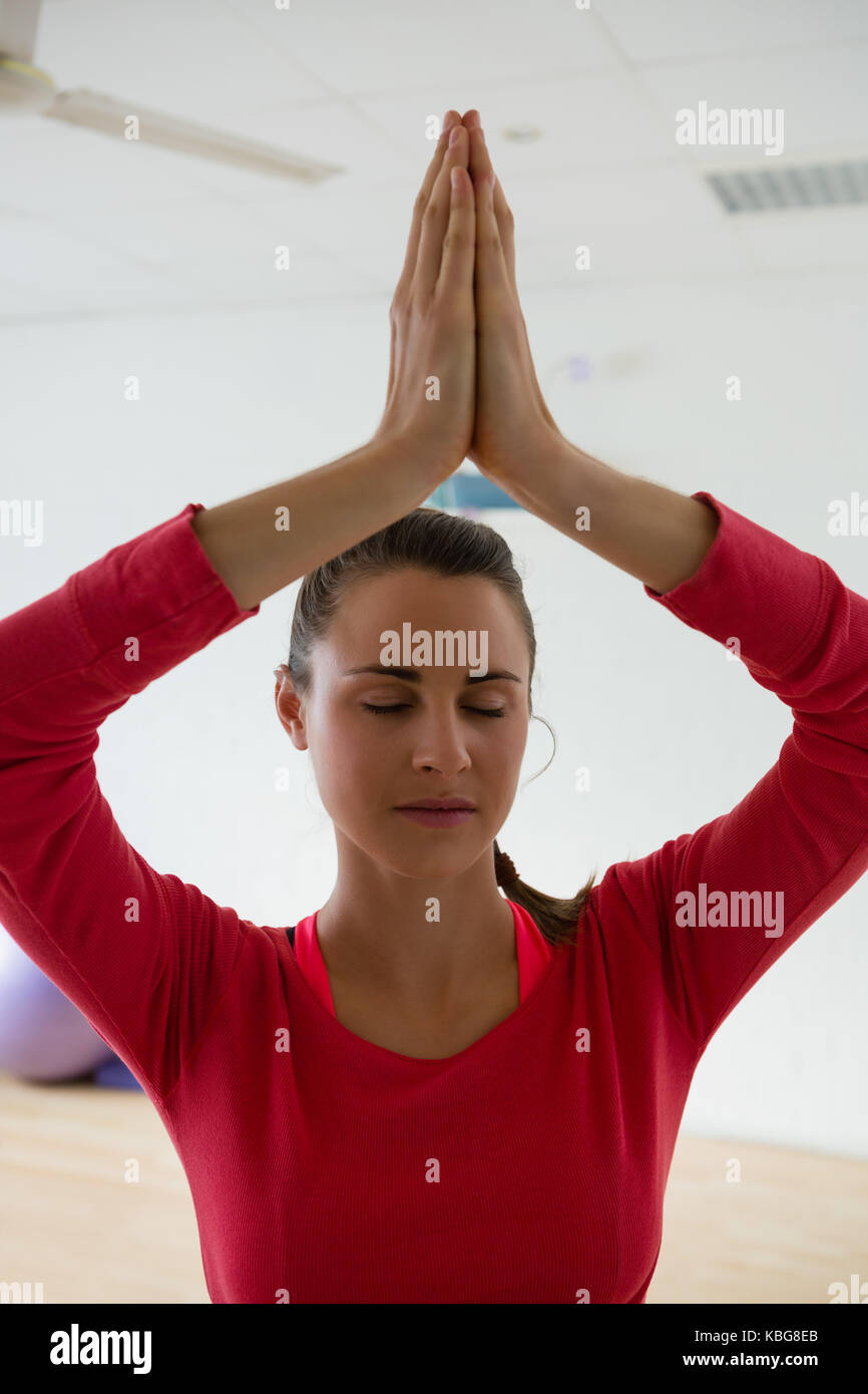 Young woman meditating while doing tree pose in yoga studio Stock Photo