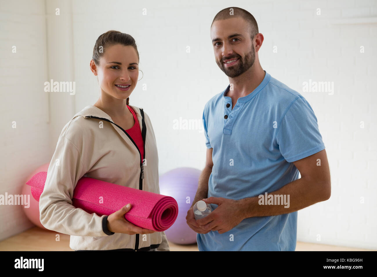 Portrait of student with instructor standing in yoga studio - Stock Image