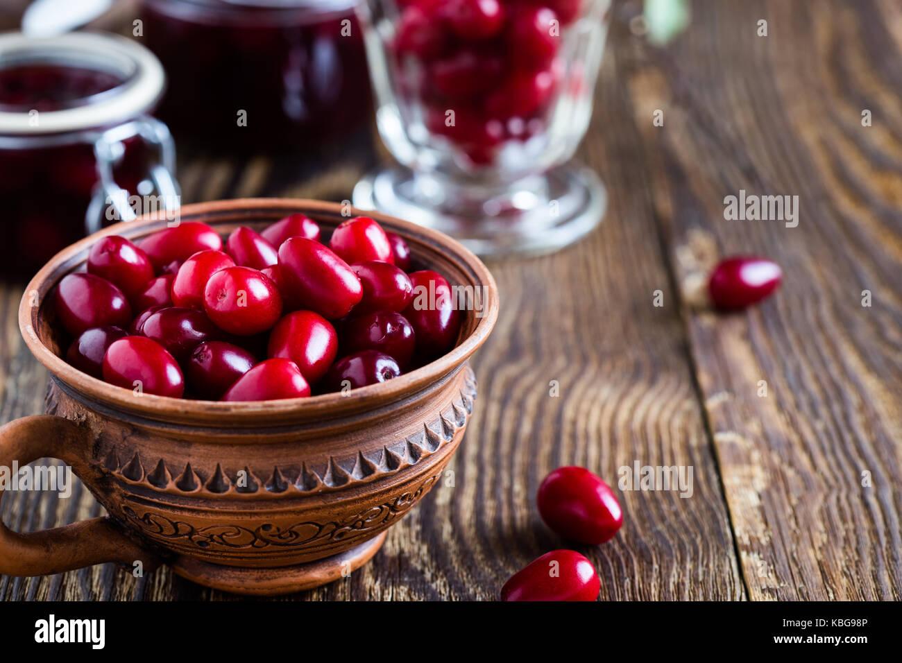 Ripe cornel berries in ceramic mug and dogwood jam on rural wooden background Stock Photo