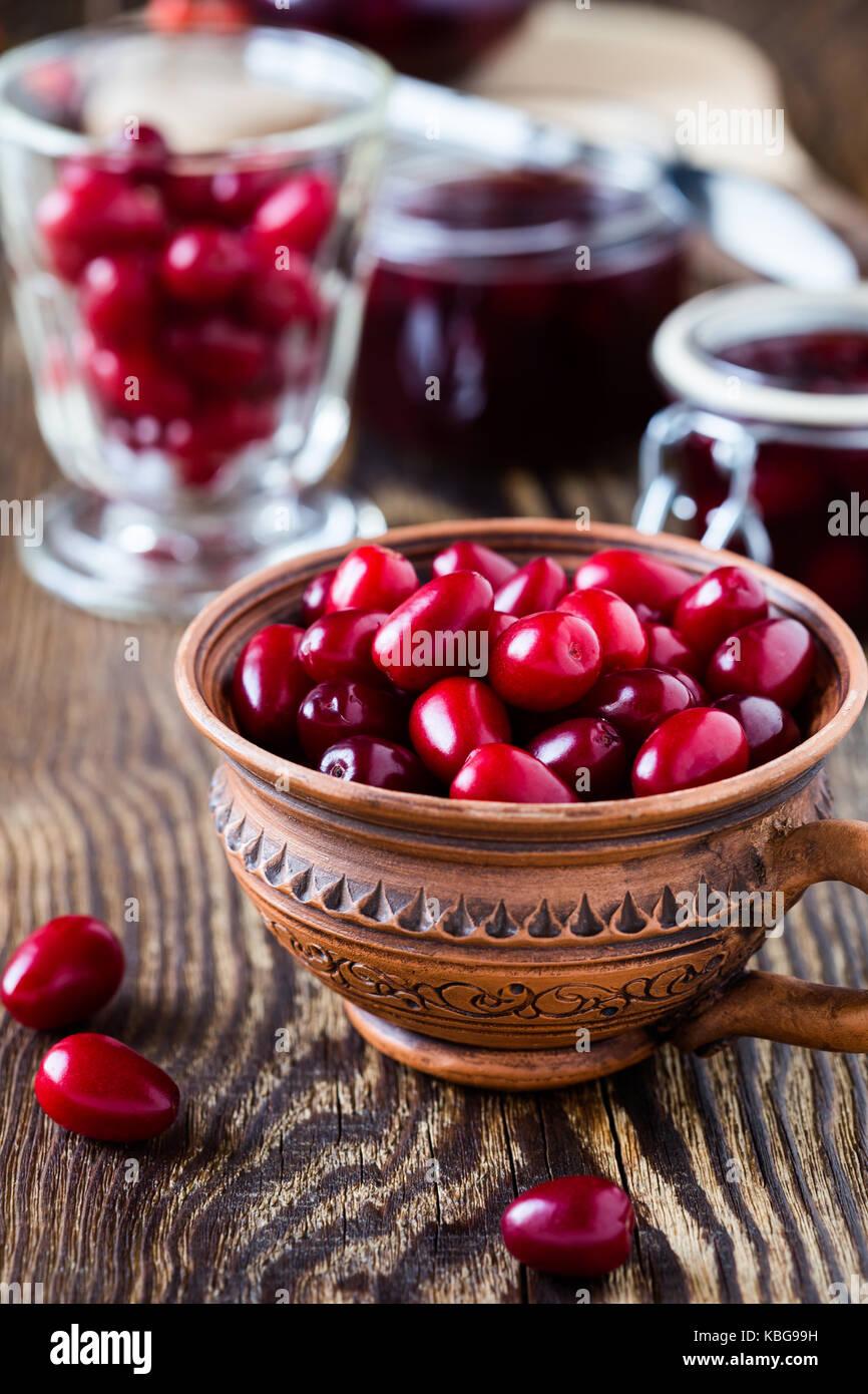 Ripe cornel berries in ceramic mug and dogwood jam on rural wooden background - Stock Image