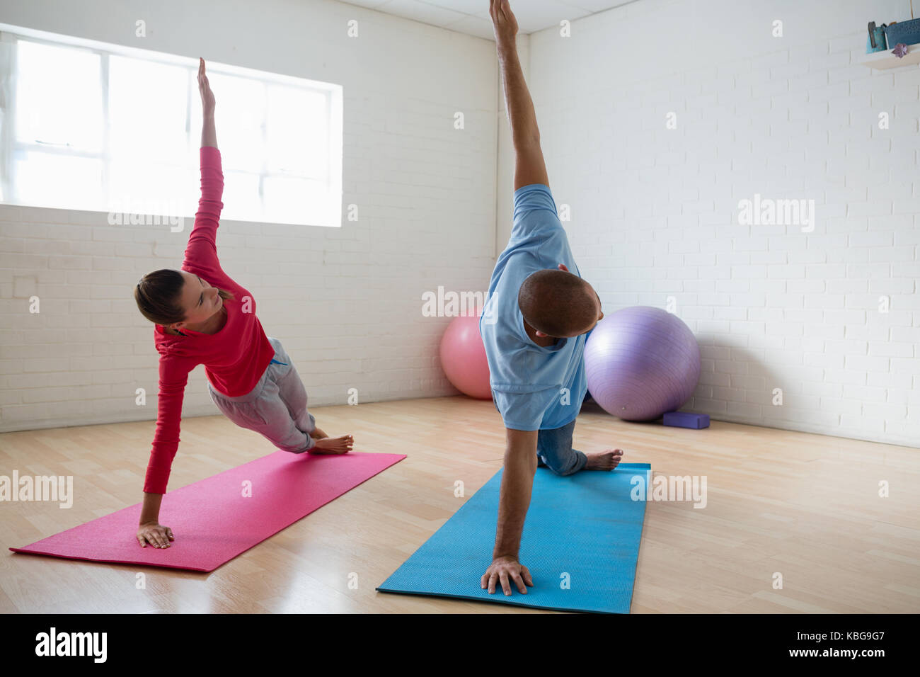 Male instructor with female student practicing side plank pose in yoga studio - Stock Image