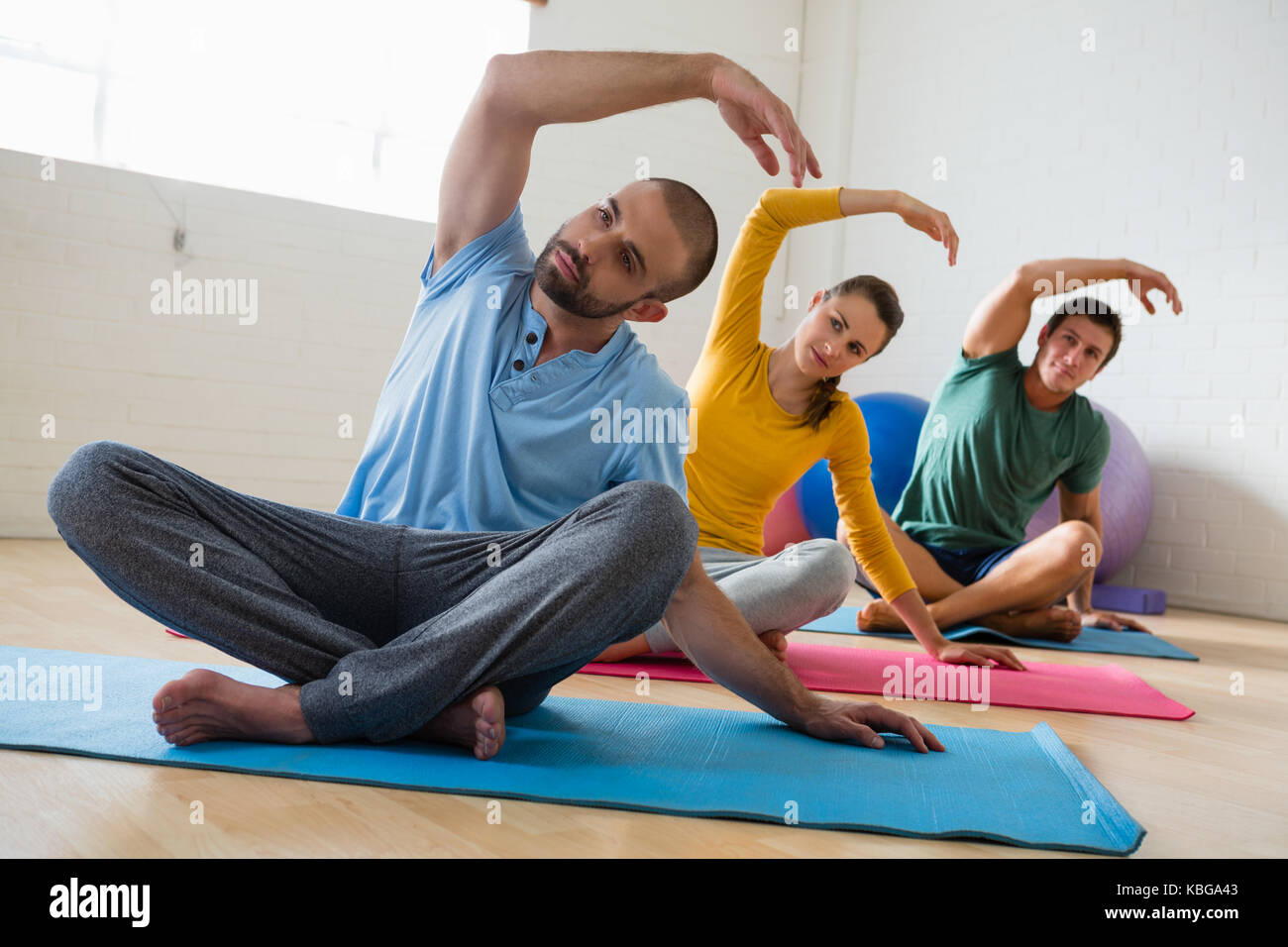 Male instructor with students exercising at yoga studio - Stock Image