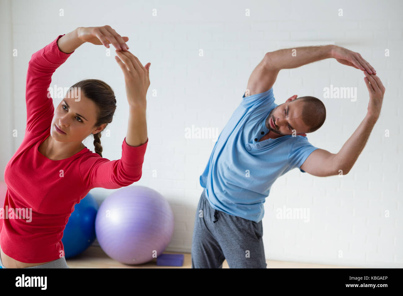 Female student with male instructor exercising in yoga studio - Stock Image