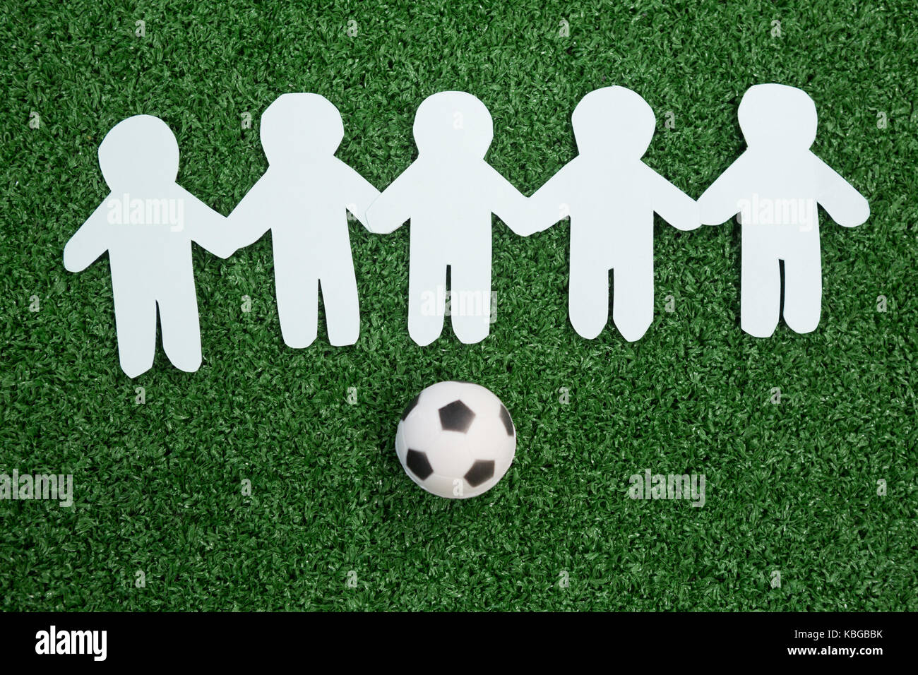 Close-up of paper cut outs and footballs arranged on artificial grass - Stock Image