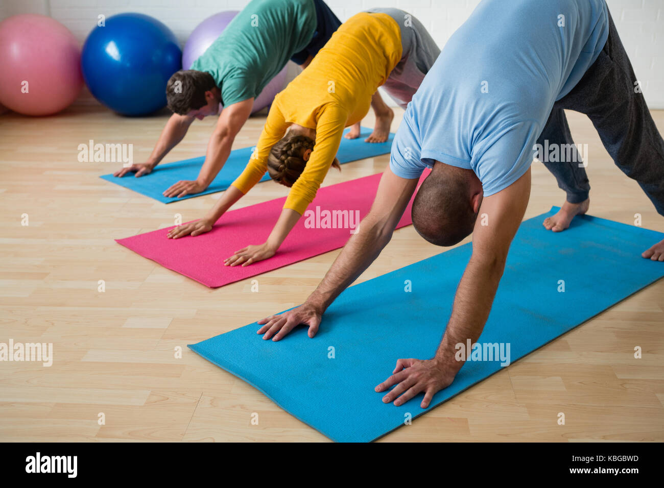 Male instructor guiding students in practicing downward facing dog pose at yoga studio - Stock Image