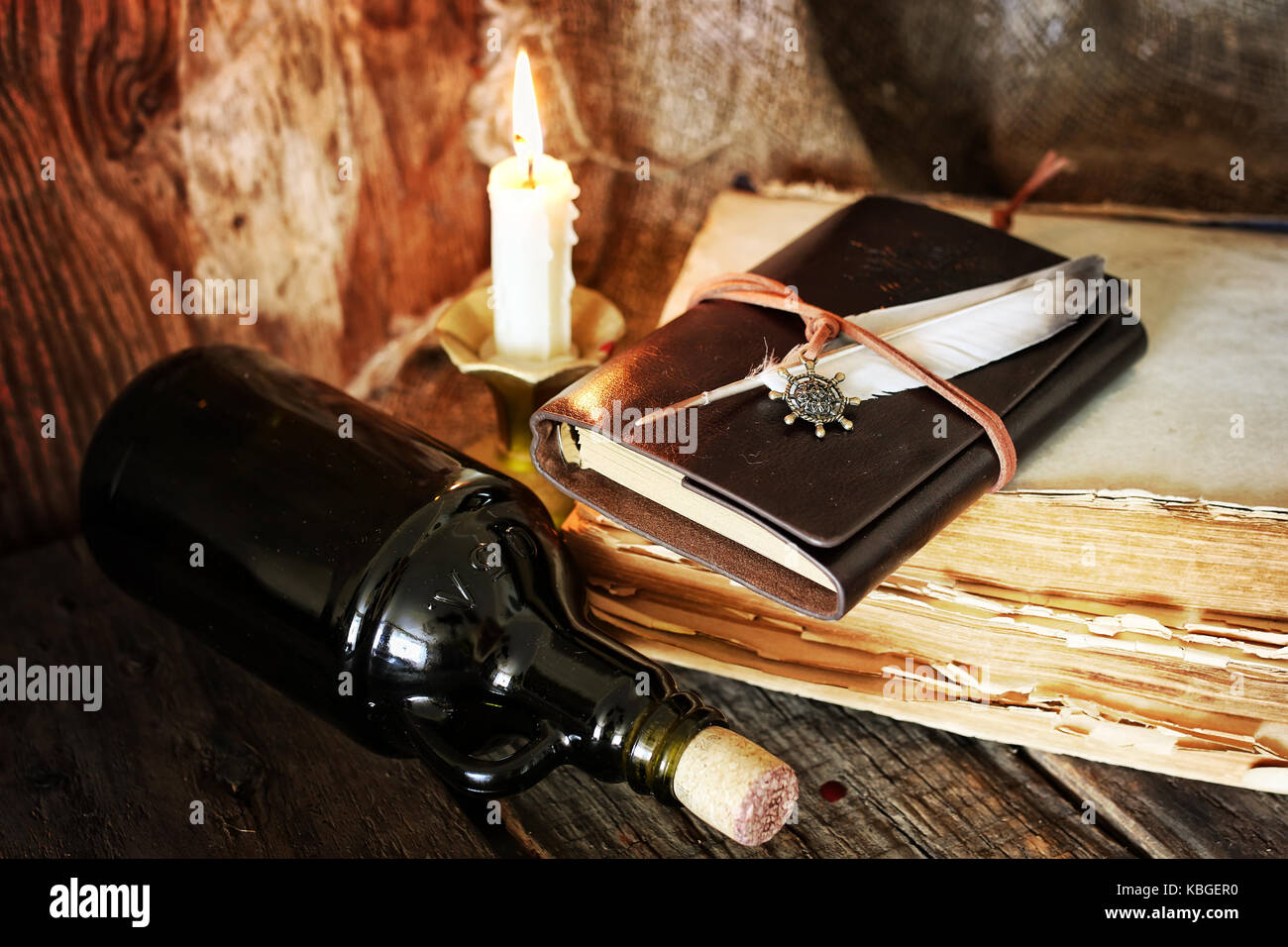 diary and feather with a bottle of rum - Stock Image