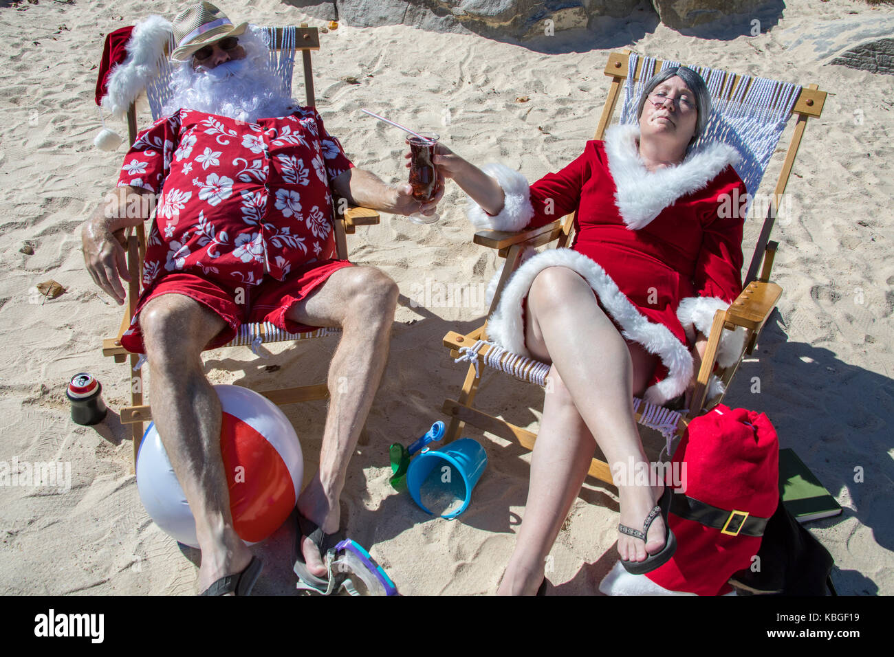 c5a9f453 Santa Claus in red swimming trunks and Hawaiian shirt lounging on sandy  beach with Mrs Claus sharing a tropical drink