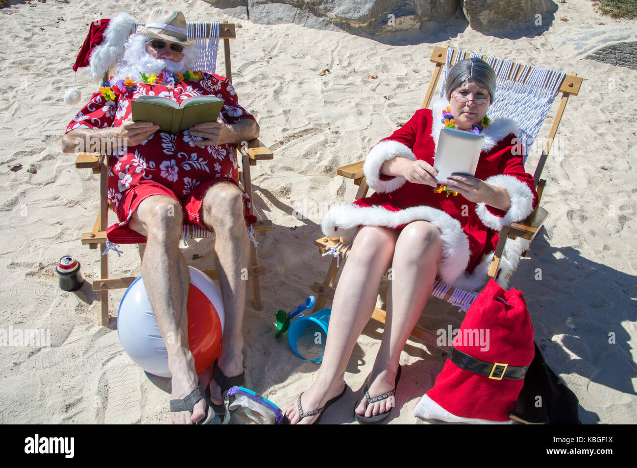 12ee77a7 Santa Claus in red swimming trunks and Hawaiian shirt lounging on sandy  beach with Mrs Claus reading on sandy beach.