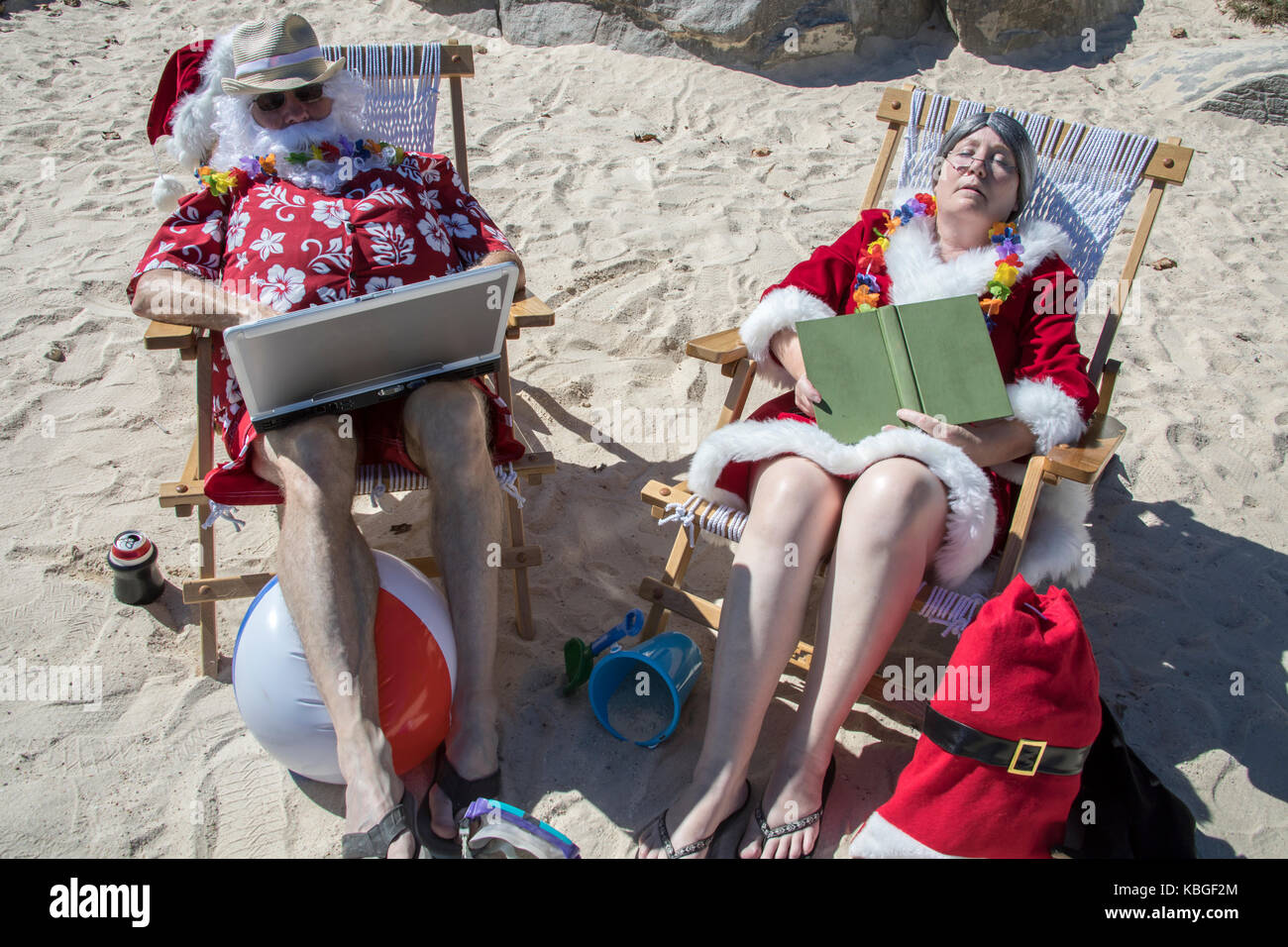 90019162 Santa Claus in red swimming trunks and Hawaiian shirt lounging on sandy  beach using laptop computer with Mrs Claus napping with a book.