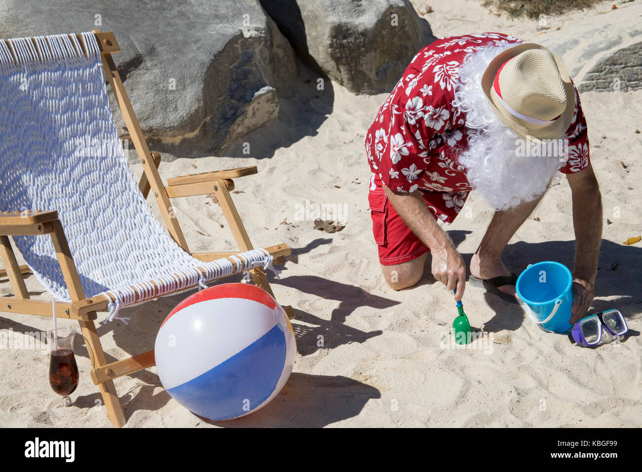 4844bbfb Santa Claus in red swimming trunks ans Hawaiian shirt lounging on sandy  beach with straw hat and sunglasses playing with shovel and pale.