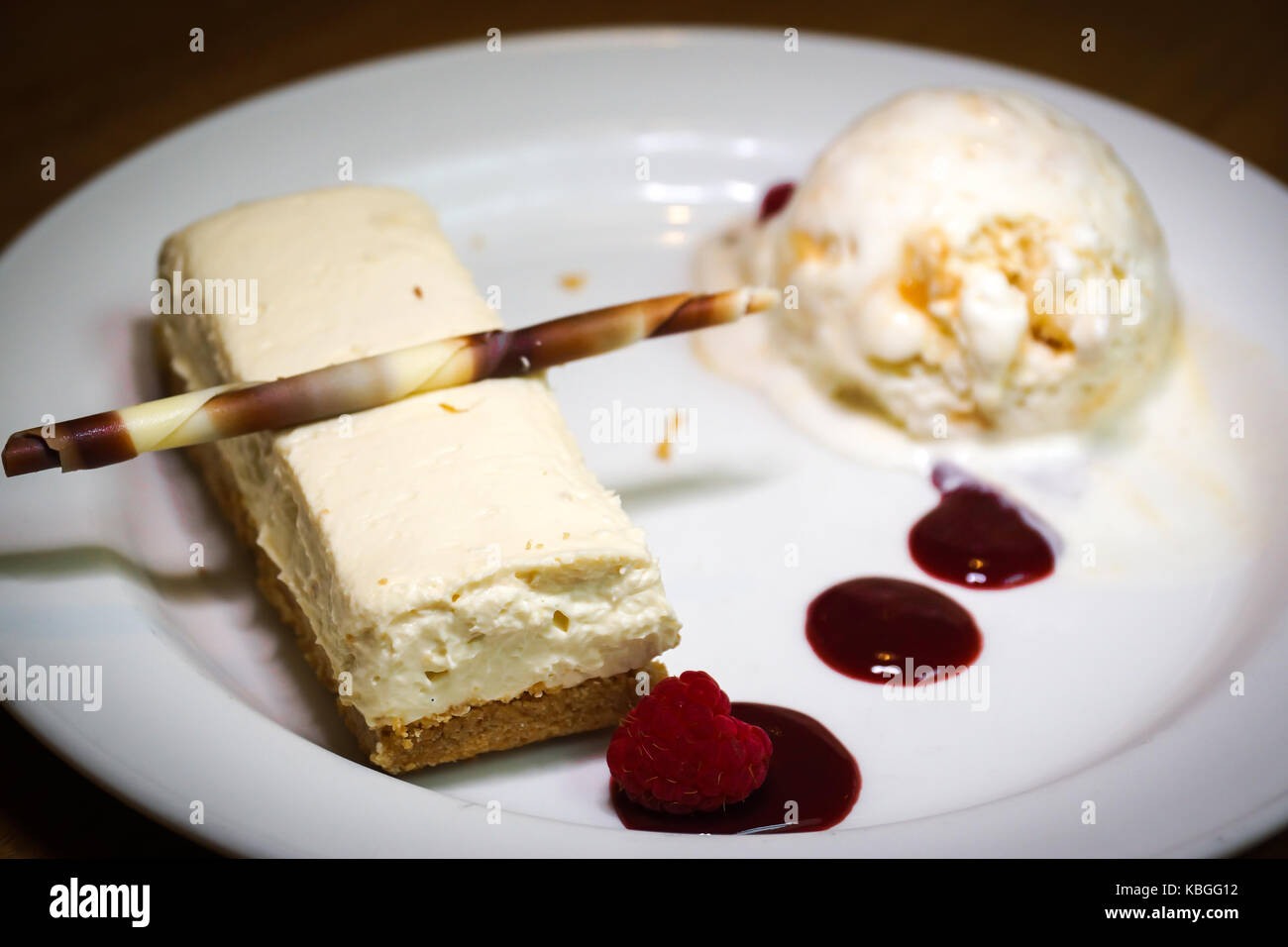 A white chocolate cheesecake paired with a vanilla honeycomb ice cream and a rasberry coulis - Stock Image