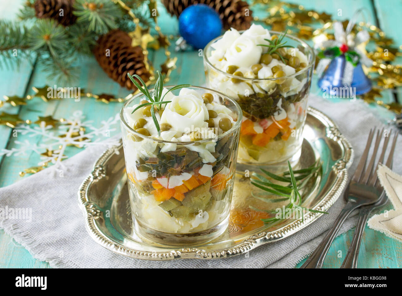 Homemade holiday snack Christmas table. Salad with marinated cucumber, potatoes, crab sticks, green peas and egg. - Stock Image