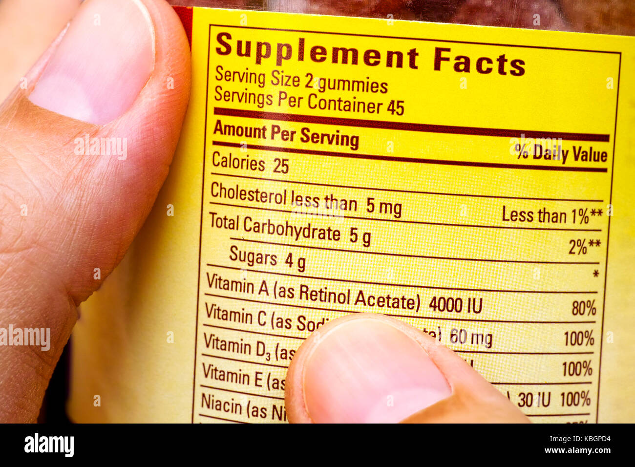 Plastic jar with supplement facts of multivitamins in woman hands. Close-up. - Stock Image