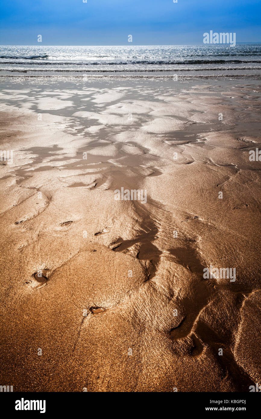 Glistening sand rivulets form abstract patterns on the beach. - Stock Image