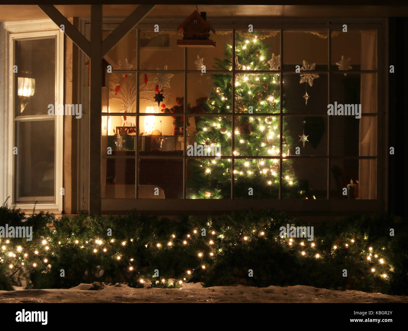 window with decorated glowing christmas tree inside a house and bright outdoor decorations night scene light blur christmas and new year holidays b