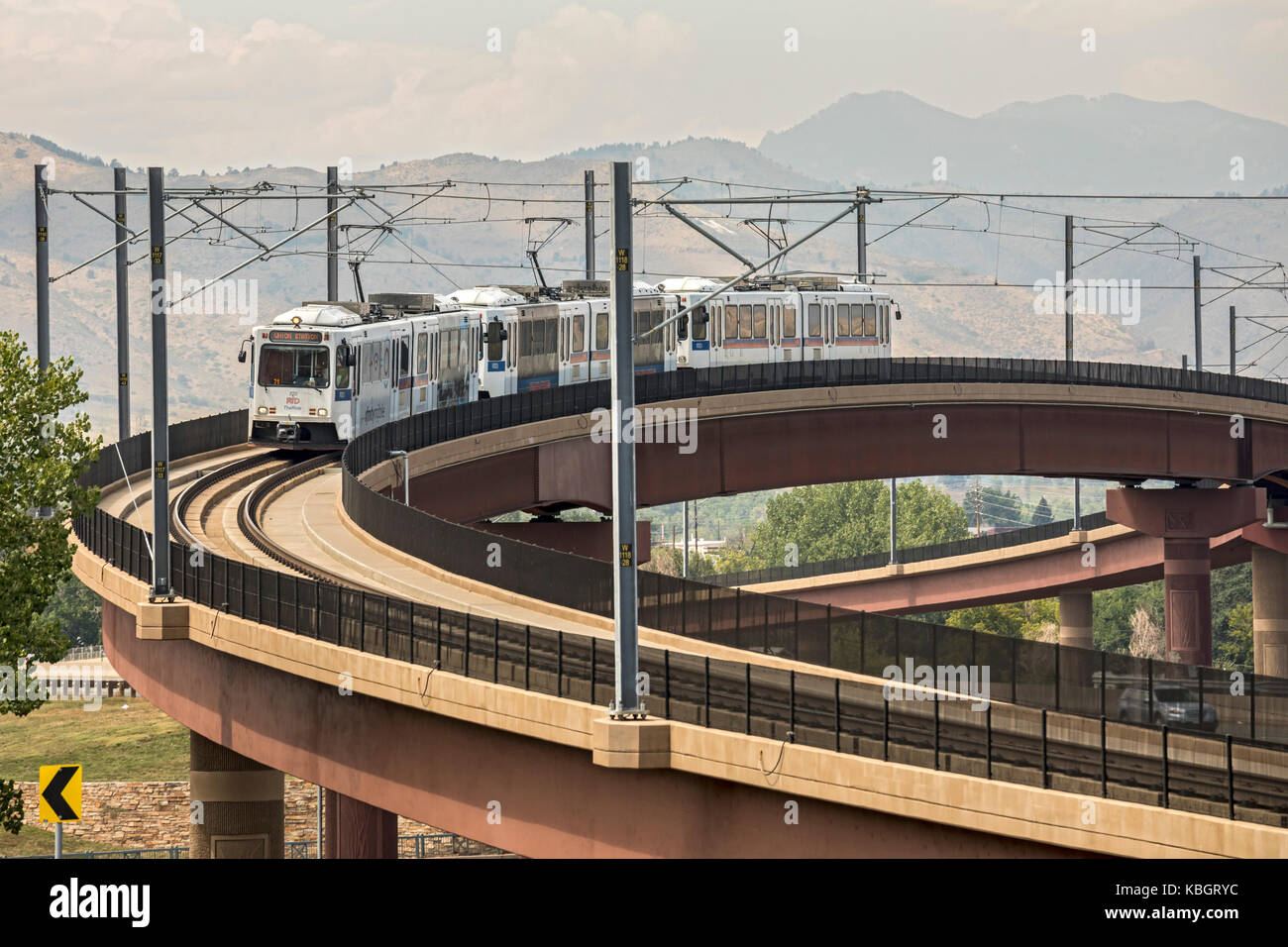 Lakewood, Colorado - A train on the 'W Line' of Denver's rapid transit system crosses a freeway. The - Stock Image