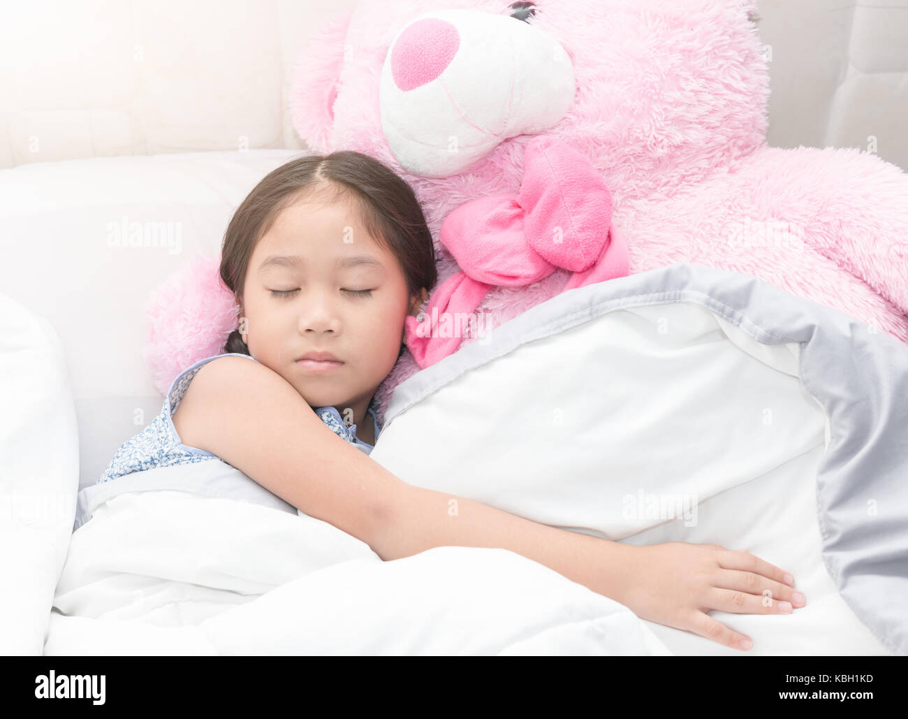 fbb66e788c8c cute asian little girl sleeping with big pink teddy bear on bed, healthy  concept
