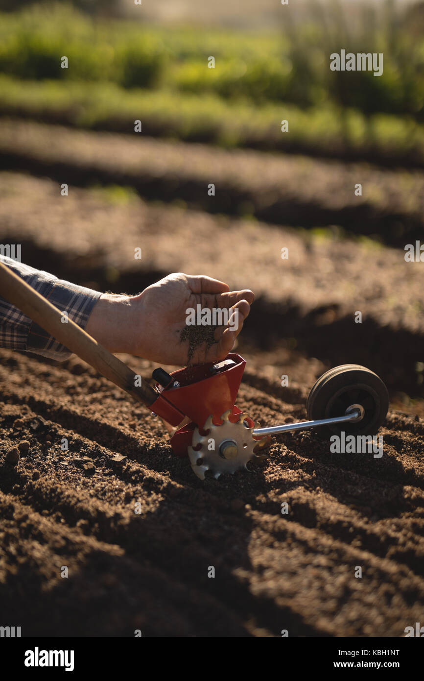 Farmer putting seeds in hand tool on a sunny day - Stock Image
