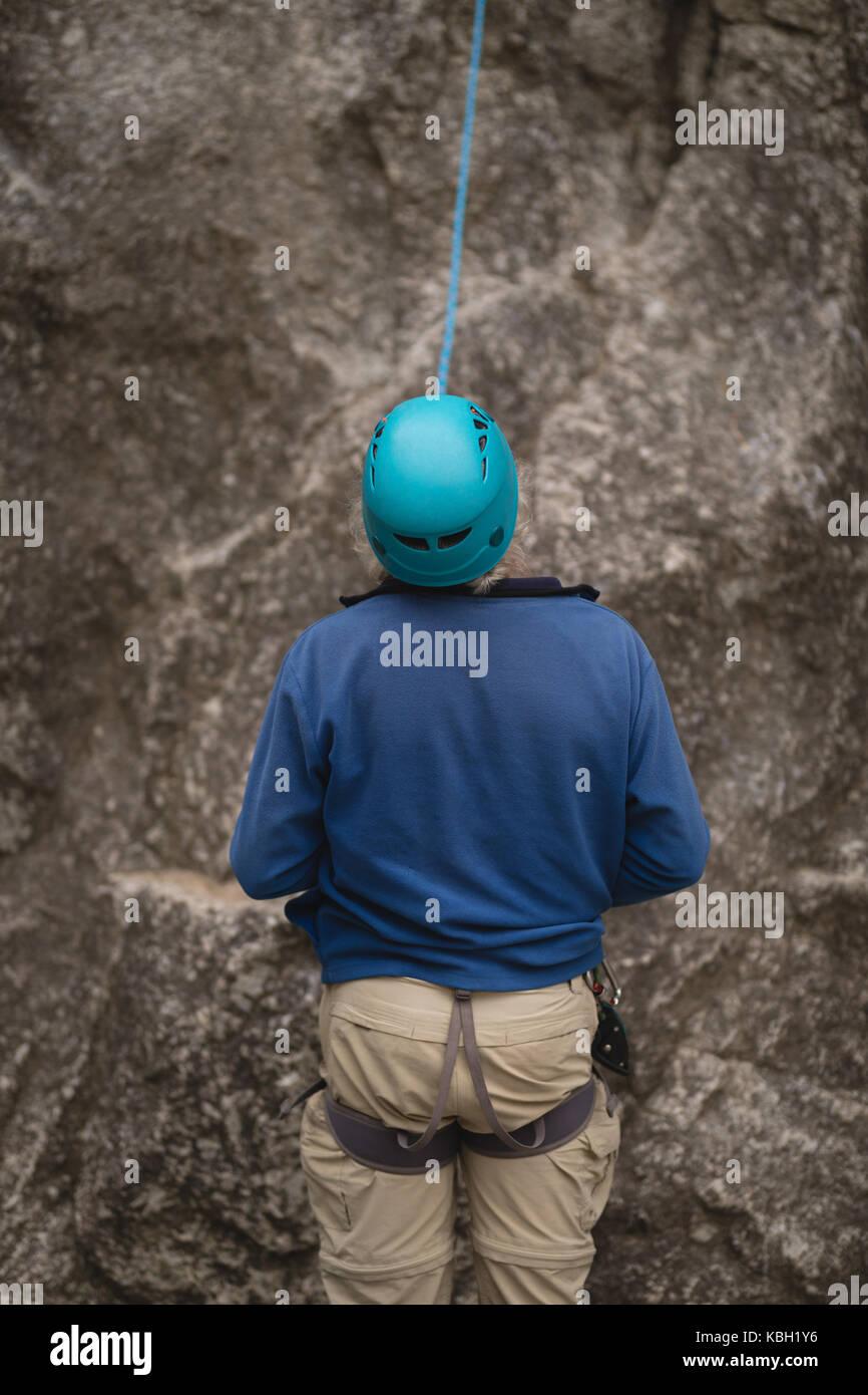 Rear view of man preparing for rock climbing - Stock Image