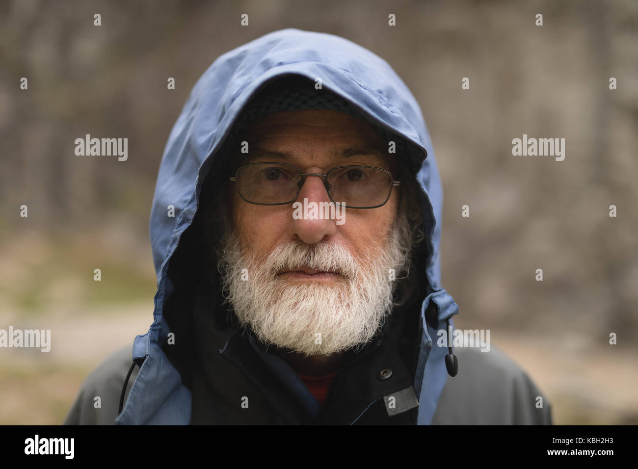 Portrait of senior man standing in front of mountain - Stock Image
