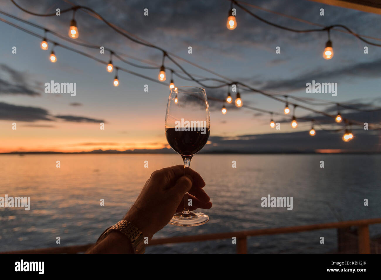 Holding up red wine under hanging deck lights at sunset over the sea. - Stock Image