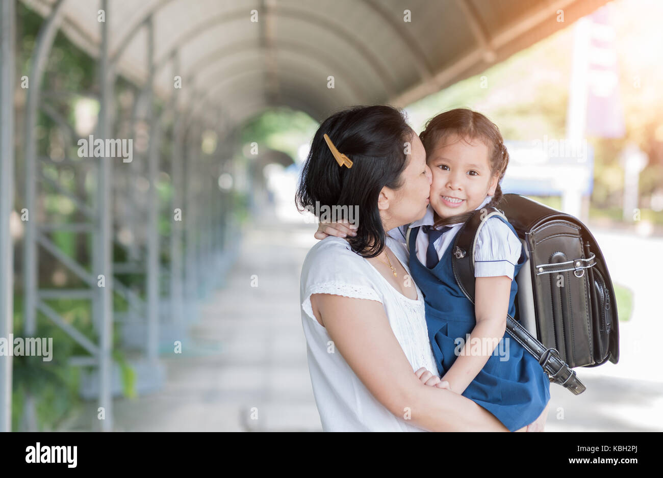 Mother kissing schoolgirl in uniform before going to school, Love and care concept - Stock Image