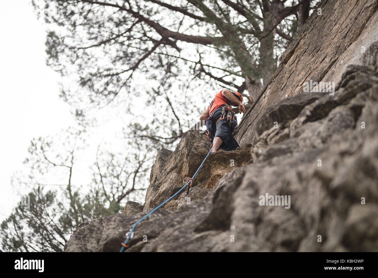 Low section of man climbing mountain - Stock Image