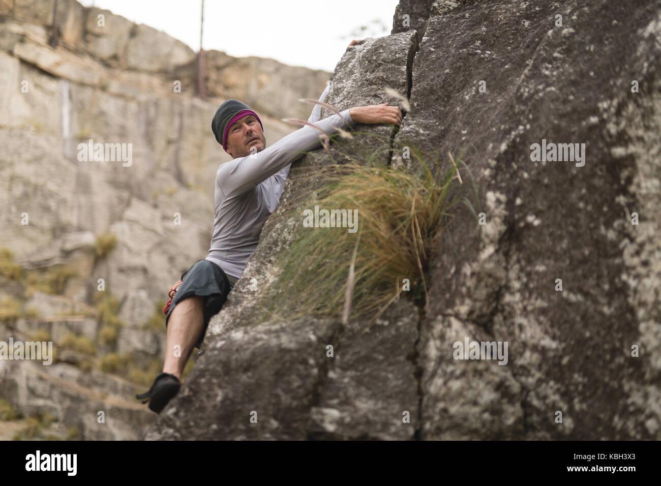 Determined man climbing mountain - Stock Image
