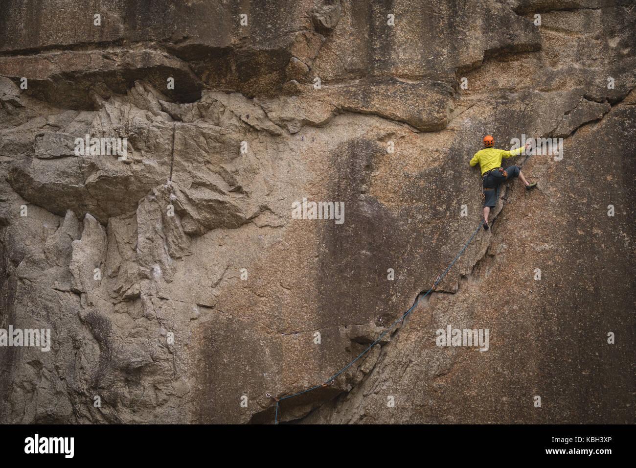 Rear view of man climbing mountain - Stock Image