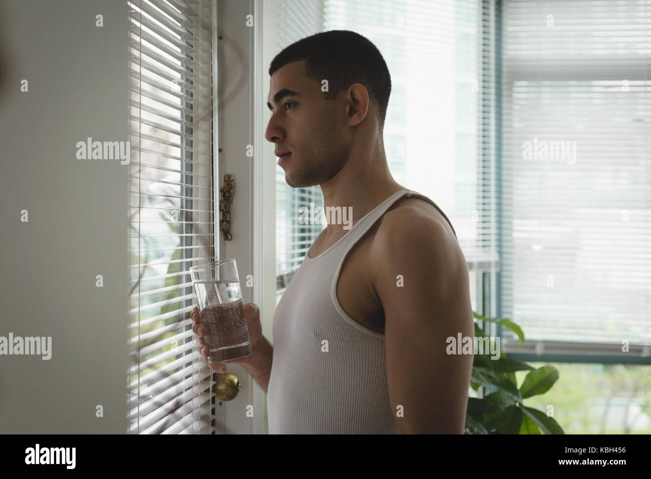 Thoughtful man looking through window blinds at home - Stock Image