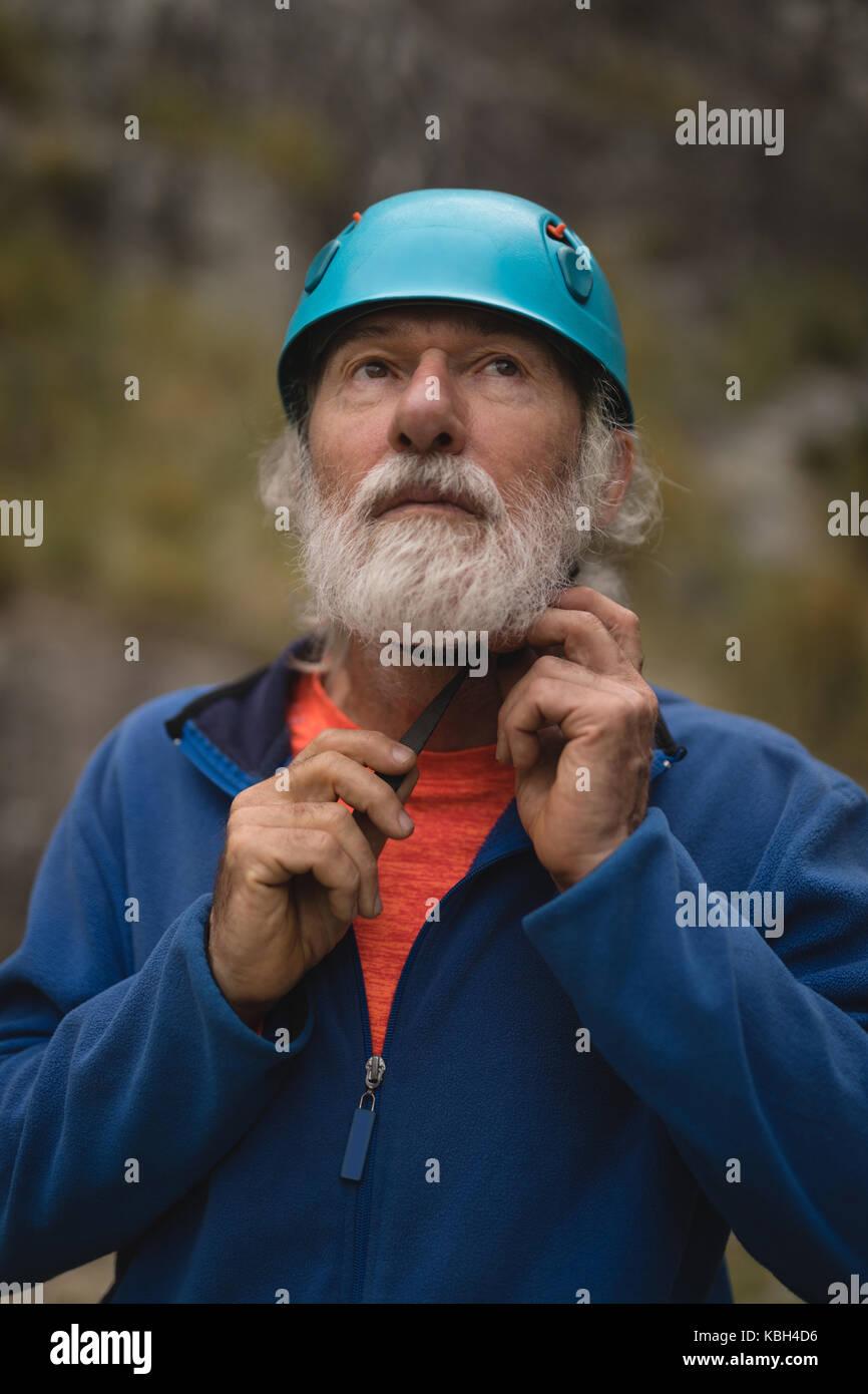 Close-up of senior man wearing protective helmet - Stock Image